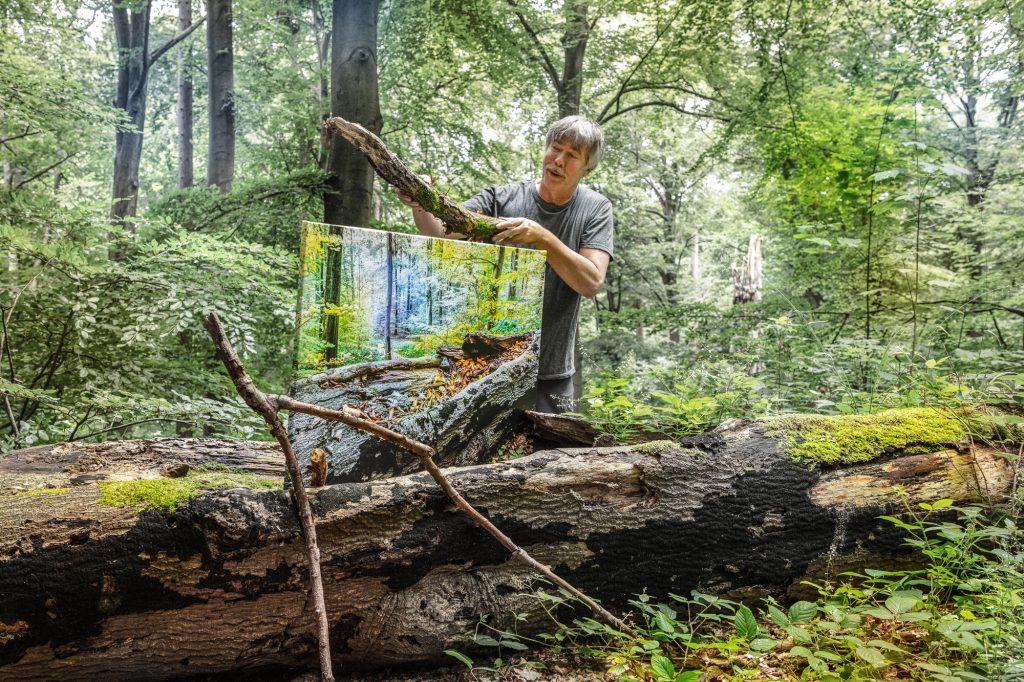 """Ingo Wandmacher mit dem Ausstellungsbild """"Friede"""" im Bad Schwartauer Riesebusch."""